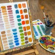 Painting color exercise mixing colors with easel brushes and palette in art painter school studio — Stock Photo #69974229