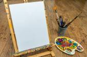 Easel palette and brushes with empty white canvas — Stock Photo