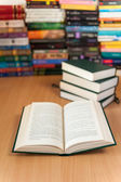 Libro abierto en el mostrador de la biblioteca con los libros apilados en el fondo — Foto de Stock