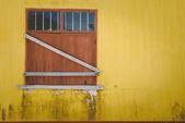 Window on yellow wall — Stock Photo