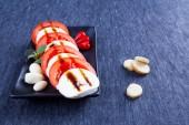 Tomato and mozzarella, black dish, design, mint, crackers, sauce — Stock Photo