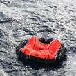 Постер, плакат: A life raft drifts in mid ocean