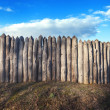 Old wooden fence against blue sky with clouds. Background — Stock Photo #74507337