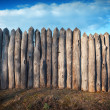 Old wooden fence against blue sky with clouds. Background — Stock Photo #74507447
