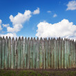 Old wooden fence against blue sky with clouds. Background — Stock Photo #74507691