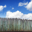 Old wooden fence against blue sky with clouds. Background — Stock Photo #74507713