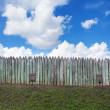Old wooden fence against blue sky with clouds. Background — Stock Photo #74507835