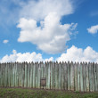 Old wooden fence against blue sky with clouds. Background — Stock Photo #74508237