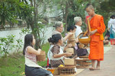 People giving alms to buddhist monks on the street,  Luang Prabang — Stock Photo