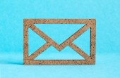 Wooden envelope icon on blue background — Stock Photo
