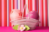 Pink and crimson Easter eggs in a basket with pink flower — Stock Photo