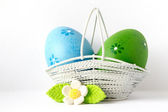 Blue and green Easter eggs in a basket with white flower — Stock Photo