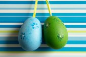 Blue and green hanged Easter eggs on striped background — Stock Photo