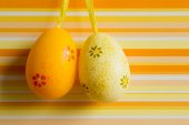 Orange and yellow hanged Easter eggs on striped background — Stock Photo