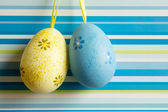 Yellow and blue hanged Easter eggs on striped background — Stock Photo