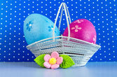 Blue and crimson Easter eggs in a basket with pink flower — Stock Photo