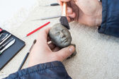 Hands of sculptor hold sculpture and clean it with brush — Stock Photo