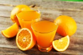 Glasses of orange juice with fruits — Stock Photo