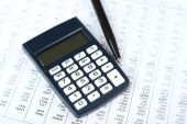 Calculator with pen on paper — Stock Photo