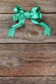 Green bow on wooden background — Stock Photo