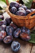 Fresh plums in basket — Stock Photo