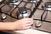Hand turn on gas stove — Stock Photo