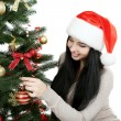 Woman decorating christmas tree — Stock Photo #65766797