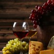 Glass of red and white wine, cheeses and grapes — Stock Photo #65914159