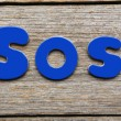 Sos word made of colorful magnets — Stock Photo #75810839