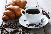 Delicious croissants with cup of coffee — Stock Photo