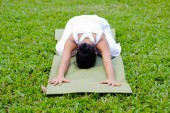 Beautiful woman practicing yoga in the park — Stock Photo