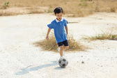 Boy play football on the dry soil ground — Stock fotografie
