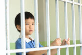 Kid at the back of the iron bar — Stock Photo