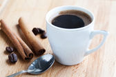 Cup of coffee, cinnamon and spoon — Stock Photo