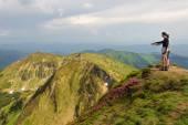 Trekker walking flowers field in mountain — Stock Photo