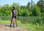 Mountain biker beside a beautiful lake — Stockfoto