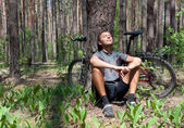 Relaxing bicyclist in coniferous forest the spring under pine tree — Stock Photo