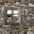 An old empty wooden window in a stone wall — Stock Photo #74685315