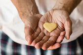 Cookie heart in human hands — Stock Photo