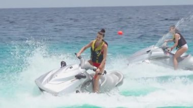 Girlfriends riding on jet skis in the sea — Stock Video