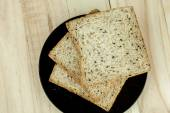 Fresh slices of wholewheat bread with various seeds and multigrain on the black plate in wood background — Stock Photo