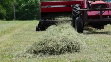A red tractor bails hay on a farm — Stock Video