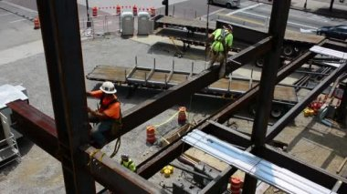 Steelworkers balance on steel support beams at a work site — Stock Video