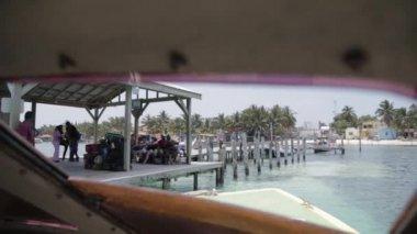 A boat docks into Caye Caulker island — Stock Video