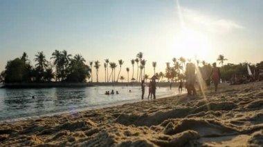 Tourists sunbath and hula hoop at sunset — Stock Video