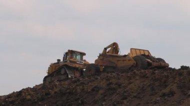A Caterpillar construction vehicle excavates soil — Stock Video