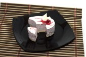 The made an incision white cake, on a black plate, on a rug — Stock Photo