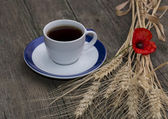 Mug of black coffee wheaten colossuses and flower — Stock Photo