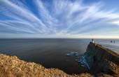 Lighthouse on a high cliff on the coast. — Stock Photo