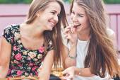 Two young female friends laugh and eat chocolate outdoors — Stock Photo